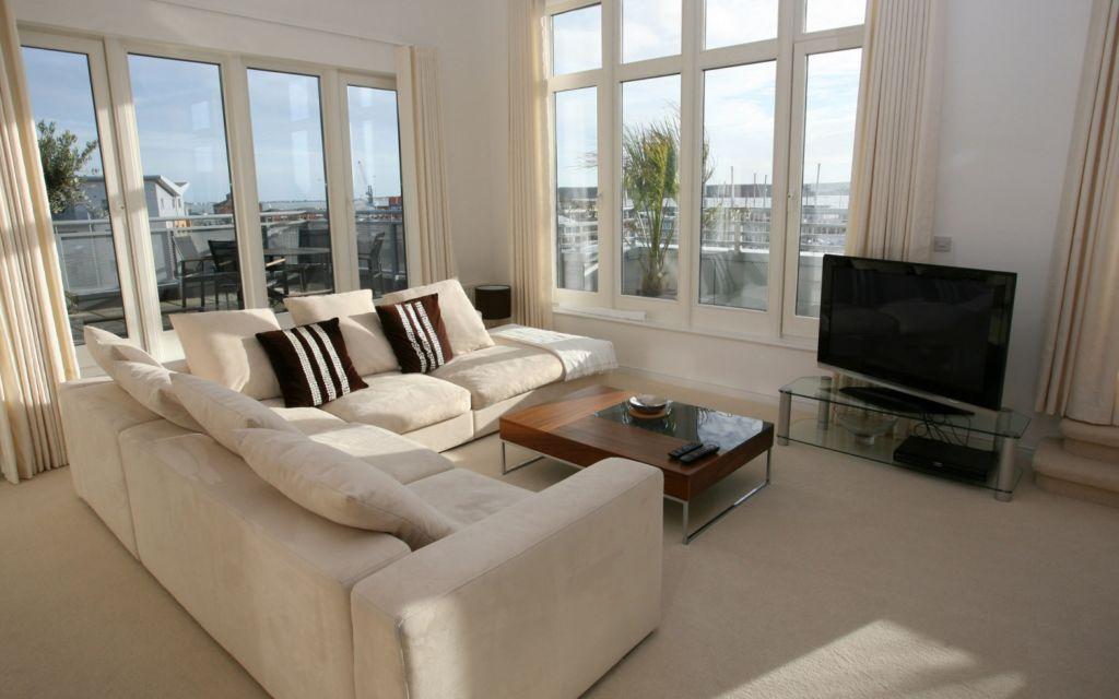 Ключевым элементом обстановки гостиной с двумя окнами является набор мебели для гостевой зоны