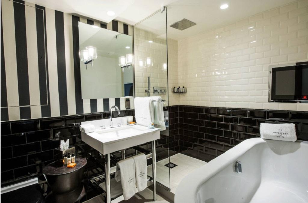 Черно-белые полосы – еще один универсальный вариант оформления стен в монохромной ванной комнате