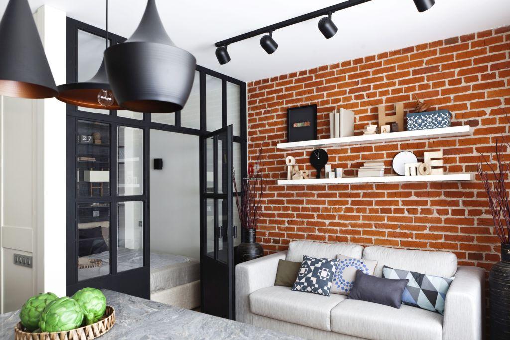 Ультрамарин в интерьере маленькой гостиной, акцент на кирпичной стене