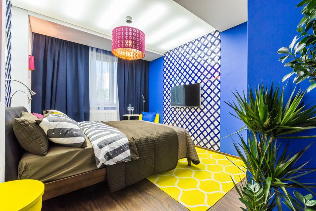 Синяя спальня с ярким ковриком желтого цвета