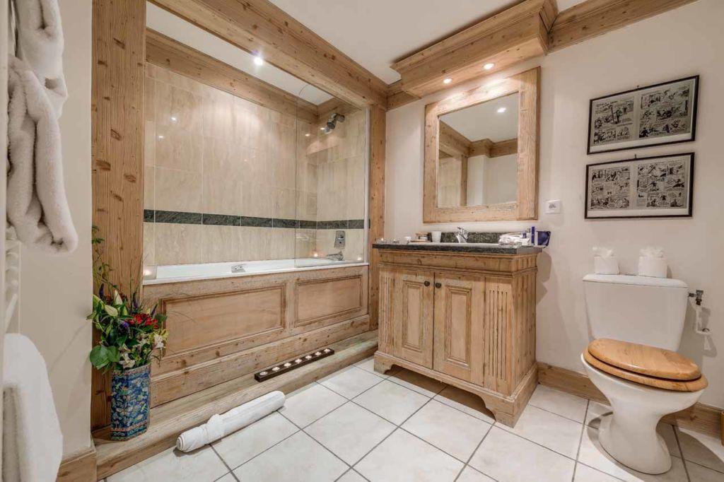 Ванная комната в стиле шале оформляется с помощью деревянных изделий светлой фактуры