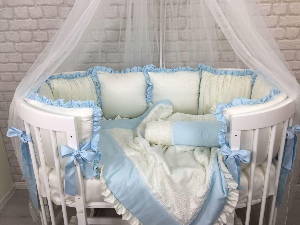 Красивая и удобная овальная кроватка с необычным оформлением в бело-голубых тонах