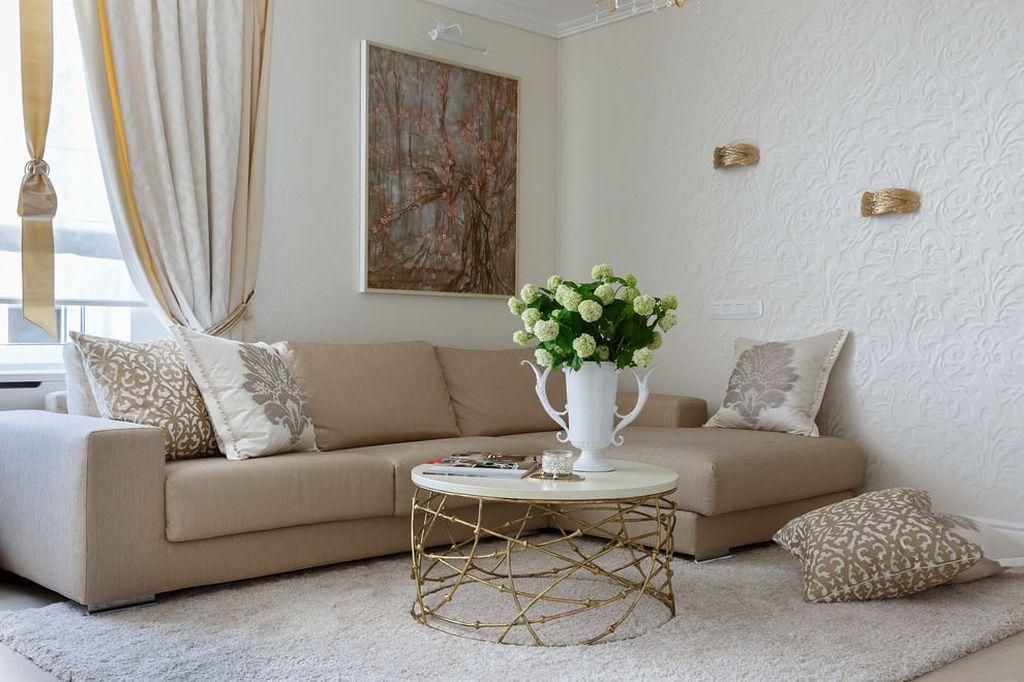 На фоне природного бежевого цвета хорошо смотрится плетеная мебель и картины