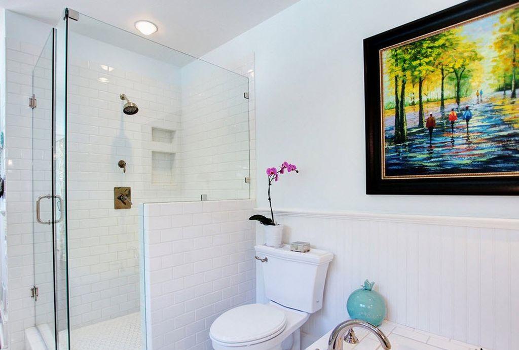 В белой ванной яркая картина будет подходящим предметом декора