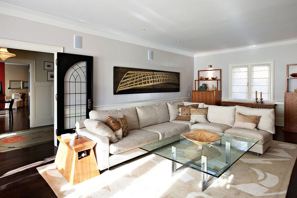 Стеклянный столик хорошо сочетается со светлой обивкой дивана
