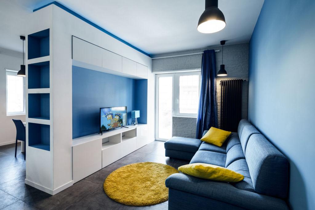 Голубая гостиная с ярким акцентом на желтый декор