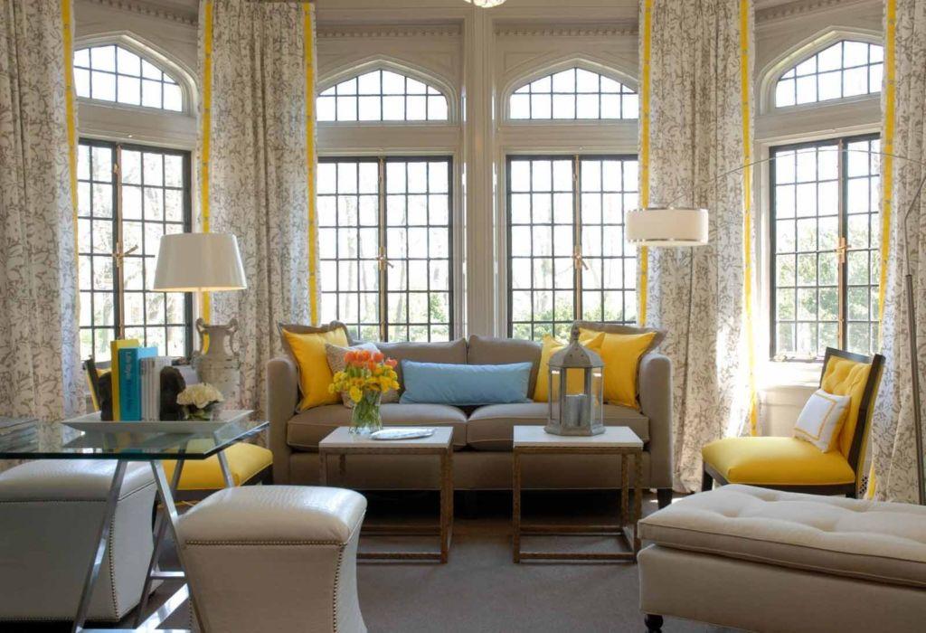 Серо желтые шторы в зале с арочными окнами и серой мебелью