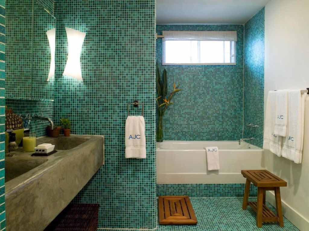Зеленая мозаика на стенах и полу может быть дополнена деревянными элементами