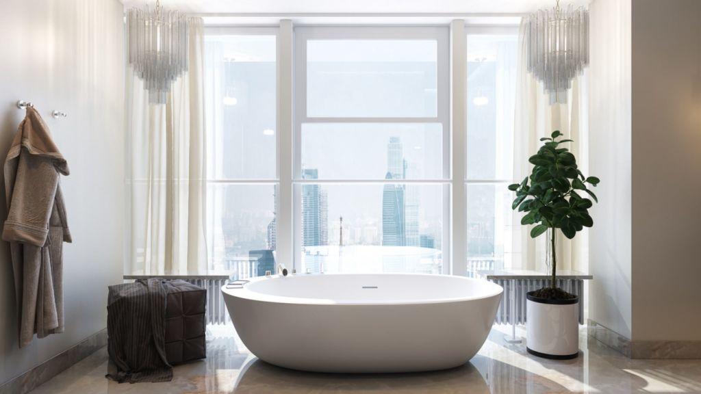 Белая ванная комната с панорамным окном и отдельно стоящей ванной