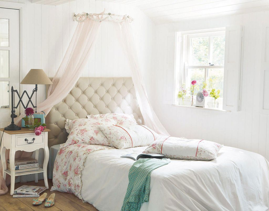 Белая спальня в стиле прованс дополняется цветочным принтом и деревянной мебелью