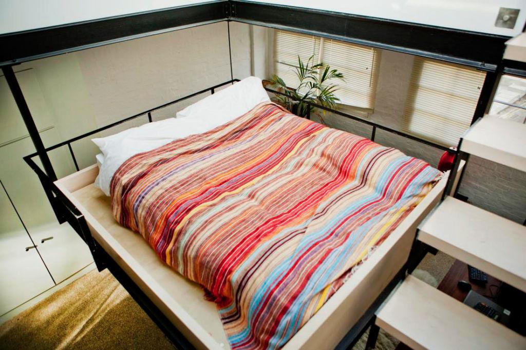 Благодаря кровати под потолком можно получить полноценную зону для сна