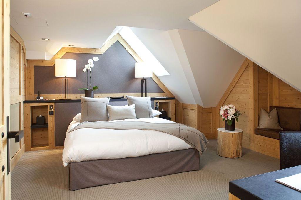 Под многоскатной кровлей кровать лучше всего поставить под мансардными окнами